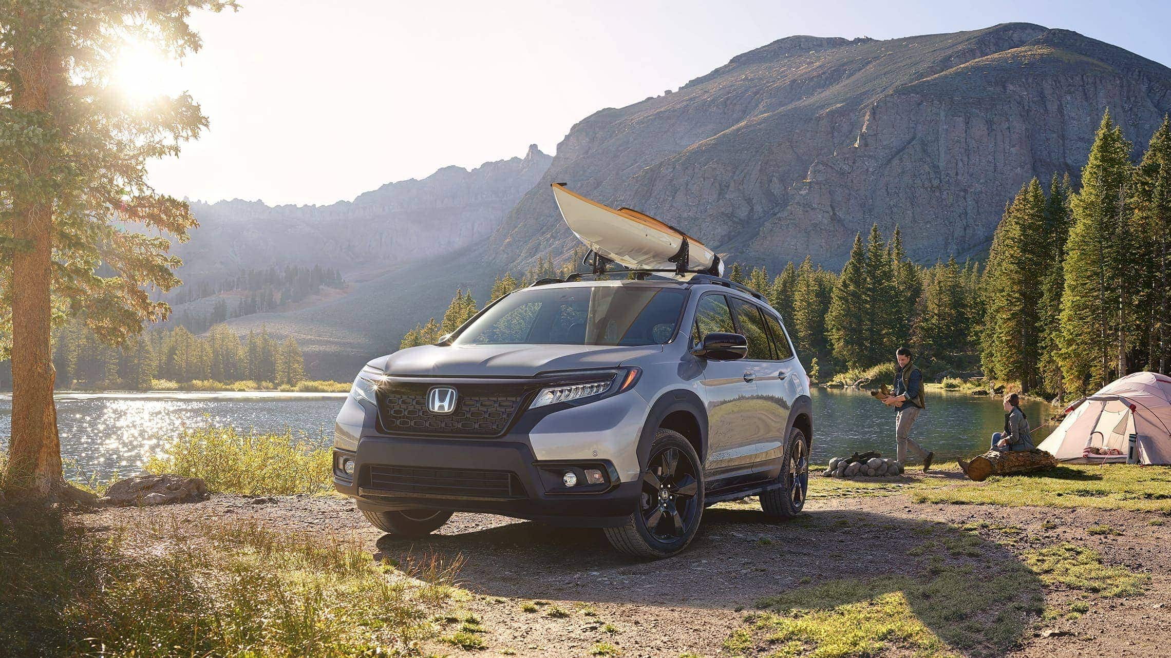Driver-side front 3/4 view of 2019 Honda Passport Elite in Lunar Silver Metallic, with accessory kayak attachment, parked at a lakeside campground with a male and female camper.