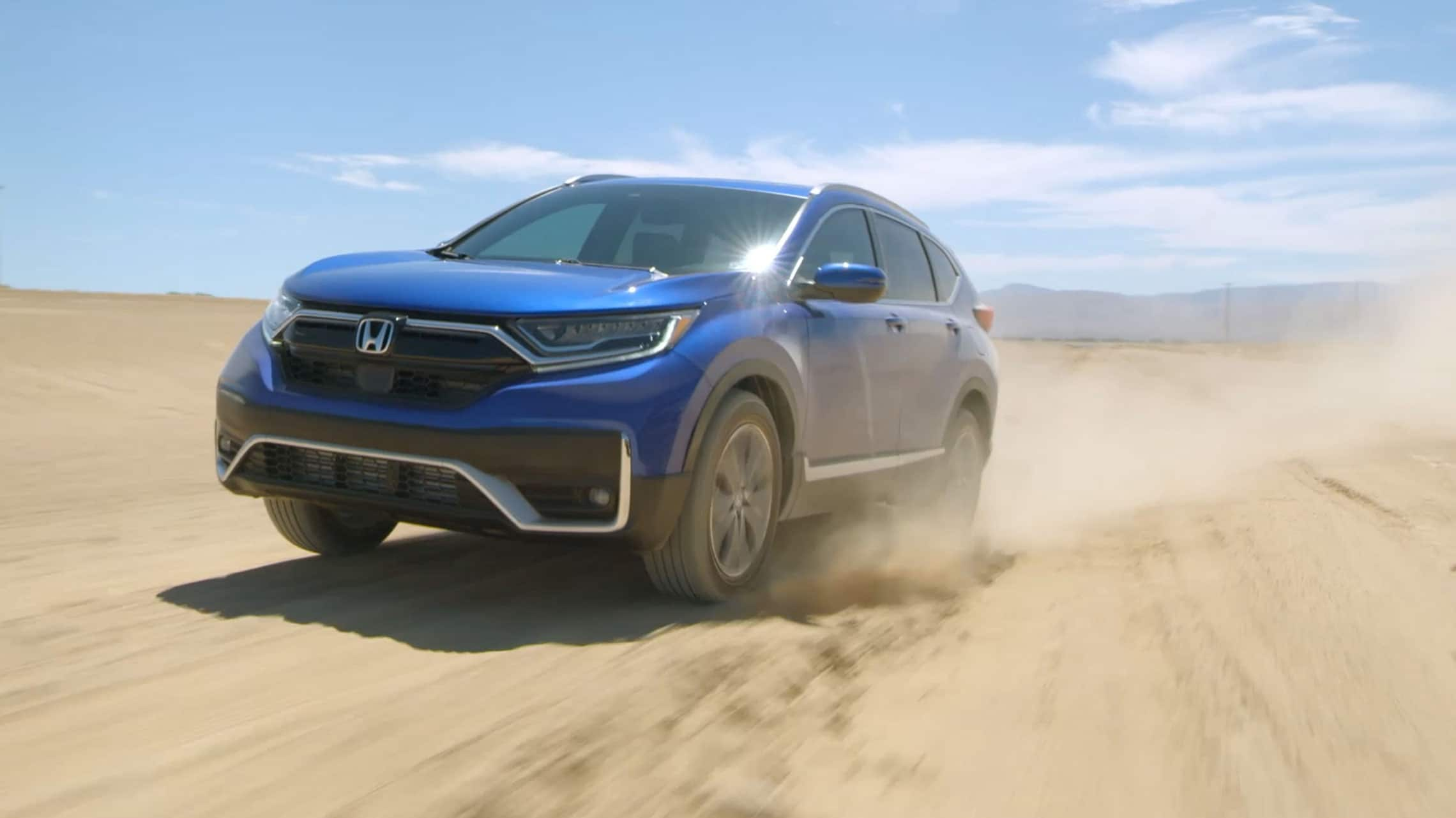 Front driver-side view of the 2021 Honda CR-V Touring with available AWD in Aegean Blue Metallic, driving on a dirt-road test course.