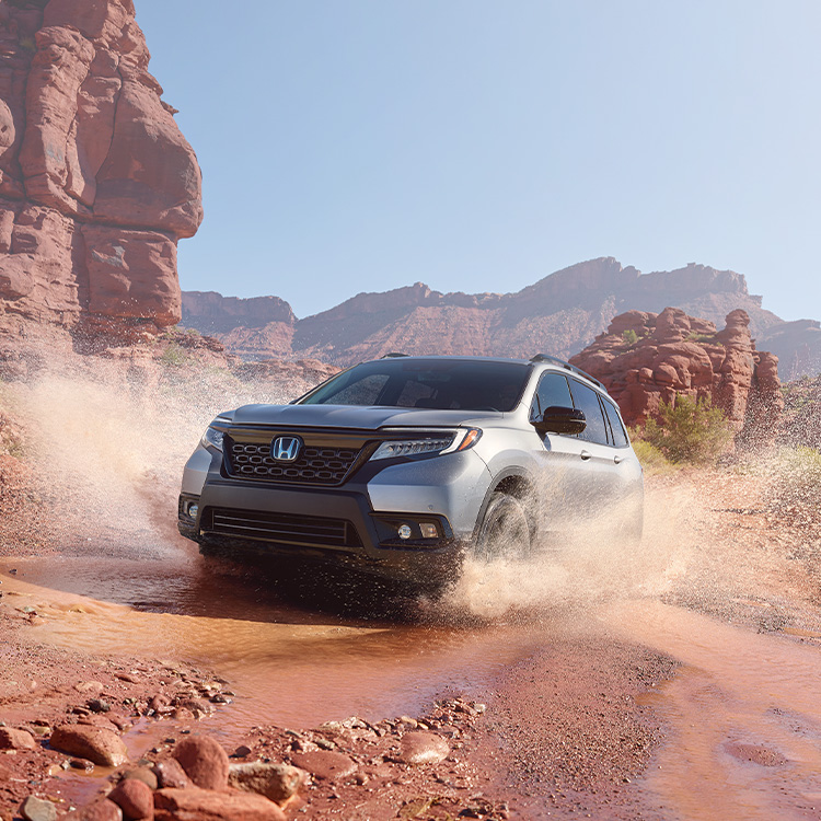 Driver-side front view of the 2021 Honda Passport Elite in Lunar Silver Metallic, demonstrating all-wheel drive and splashing through water on a rugged mountain road.