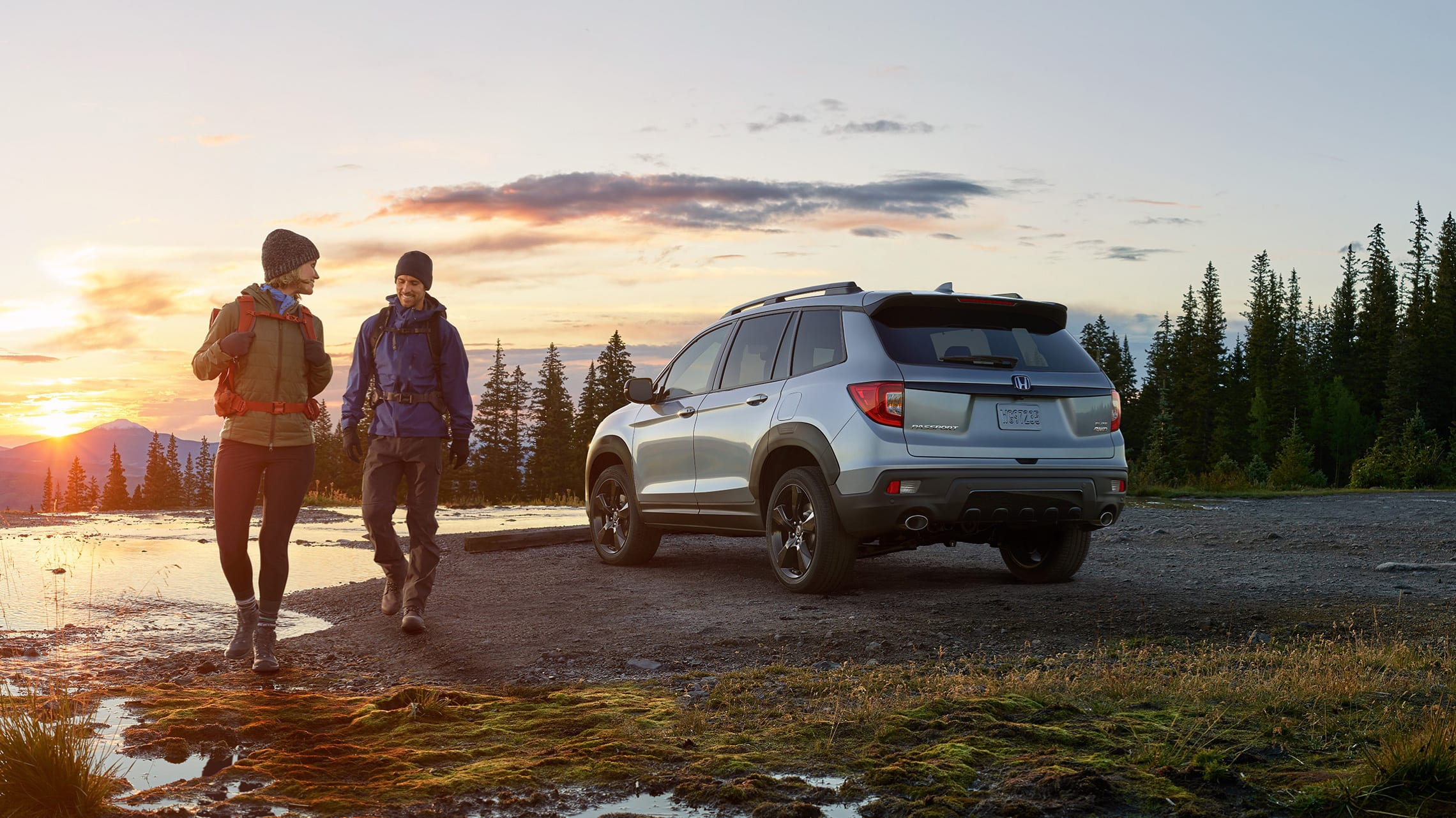 Driver-side rear view of the 2021 Honda Passport Elite in Lunar Silver Metallic with accessory fender flares, at pond location with male and female hikers in foreground.